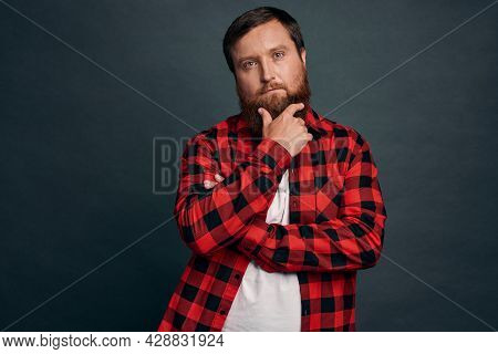 Thoughtful Young Man Picking Something In Store, Touching Chin Pensive Squinting, Considering What C