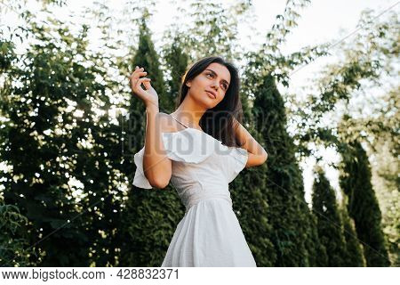 Elegant Young Brunette Woman Posing In White Summer Dress Outdoors, Low Angle View. Beautiful Slende
