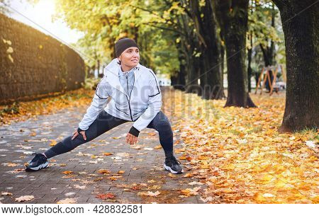 Fit Athletic Woman Doing Workout Before Jogging In Autumnal City Park On The Kids Playground. Young