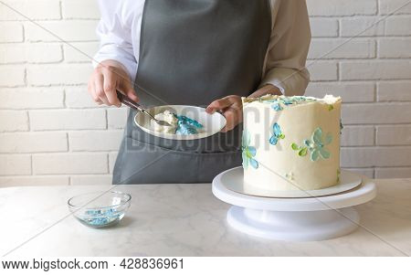 Female Baker Decorating With Cream Tasty Cake On The Table