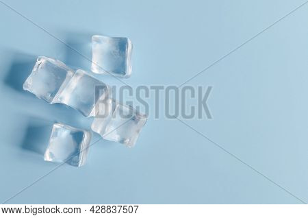 Transparent Chilled Artificial Ice Cubes On A Light Blue Background. Background Of Transparent Ice C