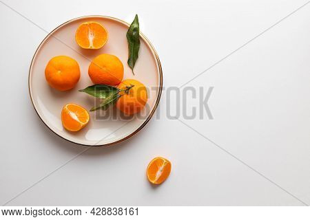 Fresh Tangerine Or Clementin Fruits On A Beige Plate With A Gold Rim On White Background. Colorful F