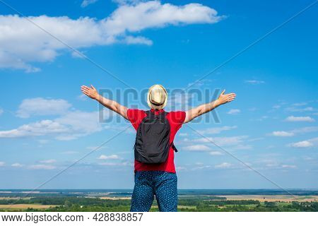 Traveler Man With Backpack,arms Outstretched Stand On Blue Sky White Cloud Summer Landscape Day.man