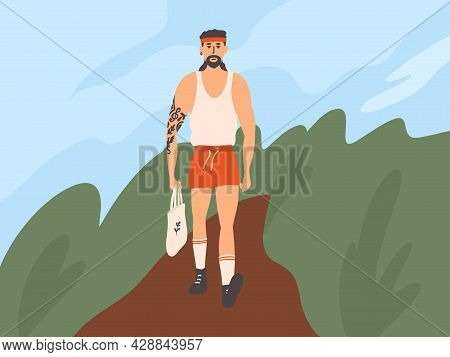 Handsome Muscular Man In Red Shorts And Undershirt Walking Down Street. Strong Guy With Tattoo Carry