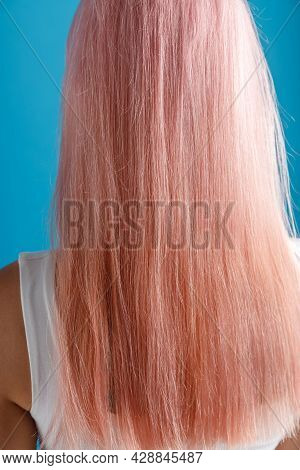 Close Up Shot Of Beautiful Sleek Natural Long Pink Color Dyed Hair Of Young Woman Standing Isolated