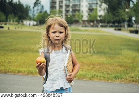 The Cute Girl, Elementary School Student, Walking To School With Bag Behind Back, Book And Apple. St