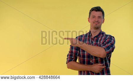 Cheerful Young Man Getting A Tip From Somebody And Showing Forefinger To The Side. Yellow Background