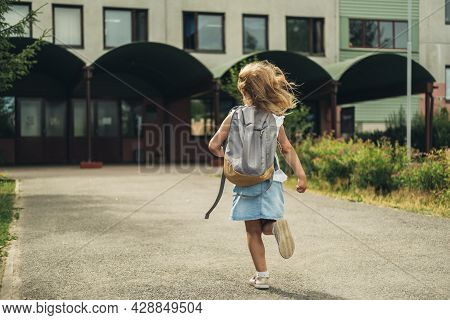 The Girl Running To School With Bags Behind Backs And Books. Students Are Ready For The New Year. Ba