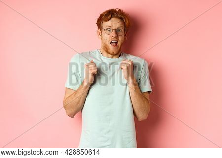 Portrait Of Scared Redhead Guy In Glasses Staring Startled At Camera, Press Hands To Body And Scream