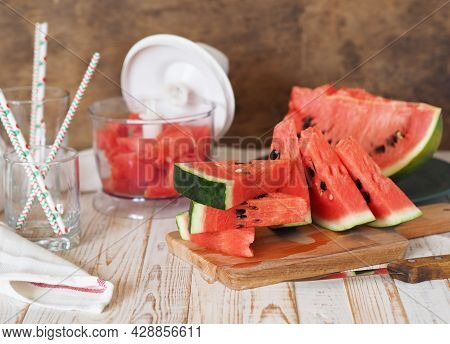 Glass Of Fresh Watermelon Juice On Table In Kitchen. Ripe Watermelons And Slices In Background. Heal