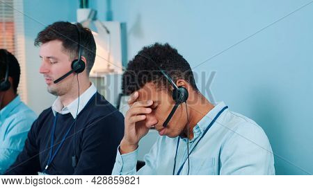 Medium Shot Of Bored And Dissatisfied Black Call Center Agent Talking To The Client On Phone. He Is