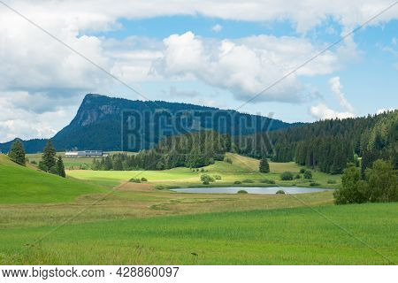 Beautiful Landscape In The Jura Mountains In Switzerland, With Grassland, A Small Lake And A Summit