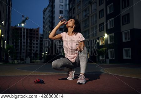 The Sportswoman Drinks Water Against The Background Of Tall Buildings. Fitness Woman Resting And Reh