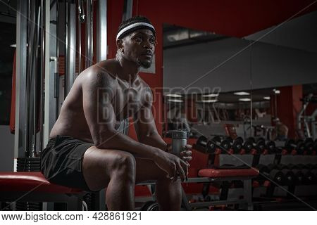 African American Sportive Man With Muscular Torso Sitting On Sports Bench With Bottle Of Water, Brea