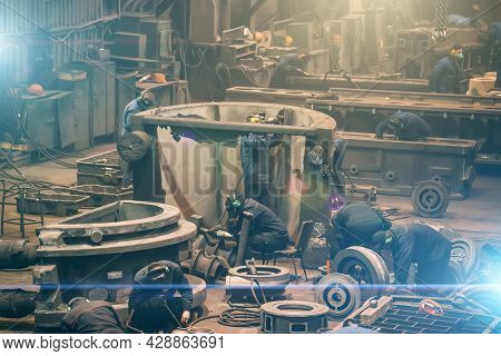 Metallurgical Plant Workplace With Many Workers Working With Cast Iron Parts, Post-casting Processin