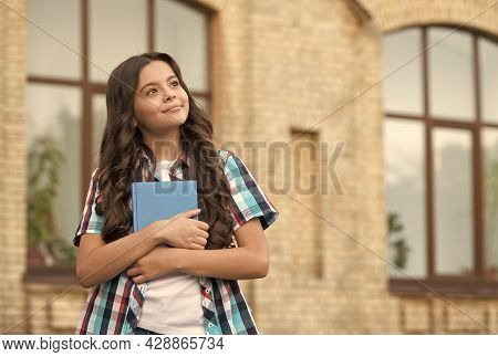Little Kid Hold School Book With Thoughtful Look In Casual Style Outdoors, Imagination, Copy Space
