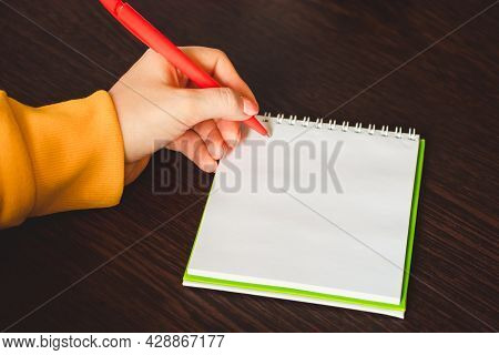 Left-handers Day. Business Woman Writes A Note In A Notebook. Girl Holds A Pen In Her Left Hand Clos