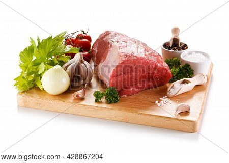 Raw Beef Chops With Lettuce And Garlic. Roast Fresh Beef Pieces On A Dark Background. Beef Chops On