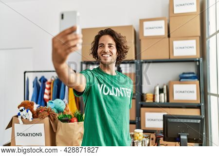 Young hispanic volunteer man smiling happy make selfie by the smartphone at charity center.