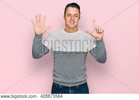 Handsome young man wearing casual winter sweater showing and pointing up with fingers number seven while smiling confident and happy.