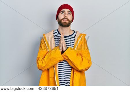 Caucasian man with beard wearing yellow raincoat begging and praying with hands together with hope expression on face very emotional and worried. begging.