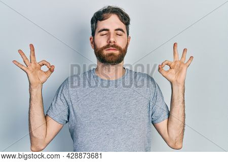 Caucasian man with beard wearing casual grey t shirt relax and smiling with eyes closed doing meditation gesture with fingers. yoga concept.
