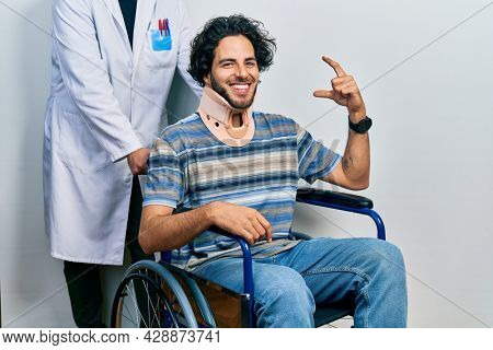Handsome hispanic man sitting on wheelchair wearing neck collar smiling and confident gesturing with hand doing small size sign with fingers looking and the camera. measure concept.