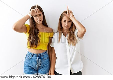 Mother and daughter together standing together over isolated background making fun of people with fingers on forehead doing loser gesture mocking and insulting.