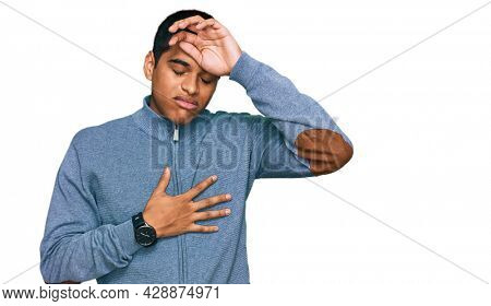 Young handsome hispanic man wearing casual sweatshirt touching forehead for illness and fever, flu and cold, virus sick