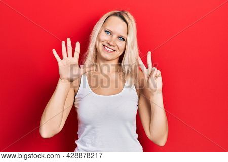 Beautiful caucasian blonde woman wearing casual white t shirt showing and pointing up with fingers number seven while smiling confident and happy.