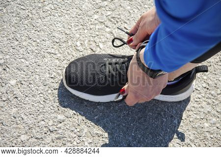 Tying Shoelaces On Black Sneakers. The Girl's Hands Tie The Sneakers