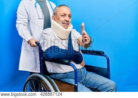 Handsome senior man with beard sitting on wheelchair with neck collar smiling friendly offering handshake as greeting and welcoming. successful business.
