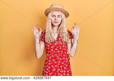 Beautiful caucasian woman with blond hair wearing summer hat relax and smiling with eyes closed doing meditation gesture with fingers. yoga concept.