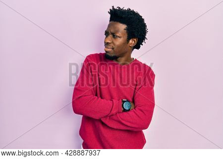 Young african american man wearing casual clothes looking to the side with arms crossed convinced and confident