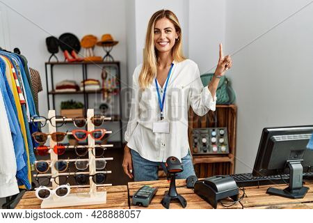 Blonde beautiful young woman working as manager at retail boutique showing and pointing up with finger number one while smiling confident and happy.