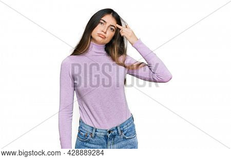 Young beautiful teen girl wearing turtleneck sweater pointing unhappy to pimple on forehead, ugly infection of blackhead. acne and skin problem