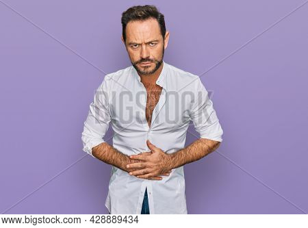 Middle age man wearing casual clothes with hand on stomach because indigestion, painful illness feeling unwell. ache concept.
