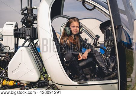 Confident Tween Girl In Pilot Headset Sitting In Helicopter Cockpit