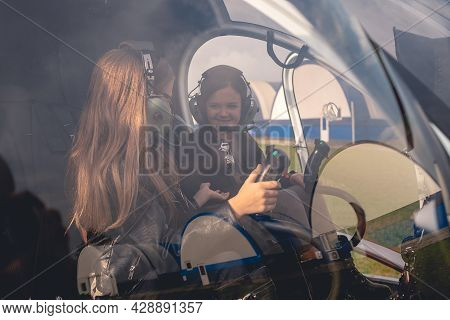 Cheerful Preteen Girls In Headsets Talking In Helicopter Cockpit