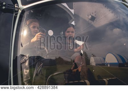 Tween Girls In Headsets Sitting On Pilot Seats In Helicopter