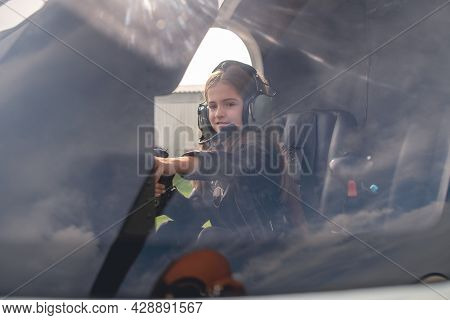 View Through Glass Of Tween Girl In Helicopter Cockpit Reaching Out To Dashboard