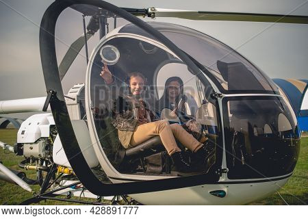Cheerful Tween Girl Pointing To Sky From Helicopter Cockpit