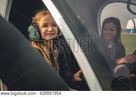 Smiling Tween Girl In Pilot Headset Sitting In Helicopter Cockpit