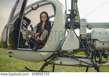 Preteen Girl In Mirrored Sunglasses Sitting In Open Helicopter Cockpit