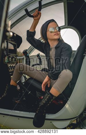 Tween Girl In Mirrored Sunglasses Sitting On Pilots Seat In Open Helicopter