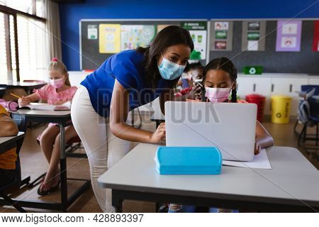 African american female teacher wearing face mask teaching a girl to use laptop at elementary school. back to school and education concept