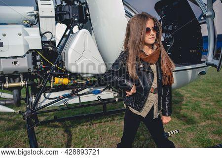 Confident Tween Girl In Sunglasses Standing Near Open Helicopter