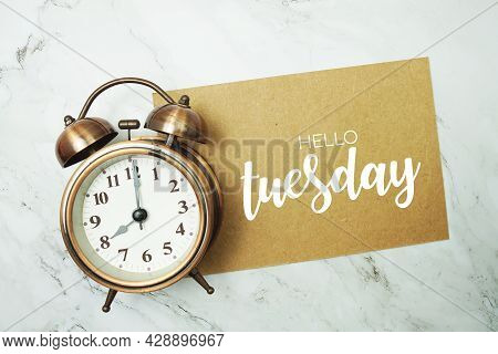 Hello Tuesday Typography Text On Paper Card With Alarm Clock On Marble Background