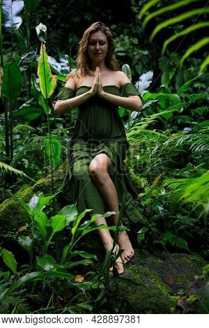 Woman In Jungle Sitting On A Stone Surrounded By Lush Green Plants. Hands In Namaste Mudra, Closed E