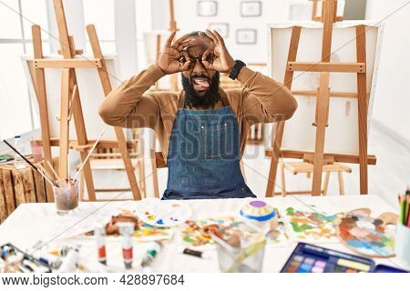 African american artist man at art studio doing ok gesture like binoculars sticking tongue out, eyes looking through fingers. crazy expression.